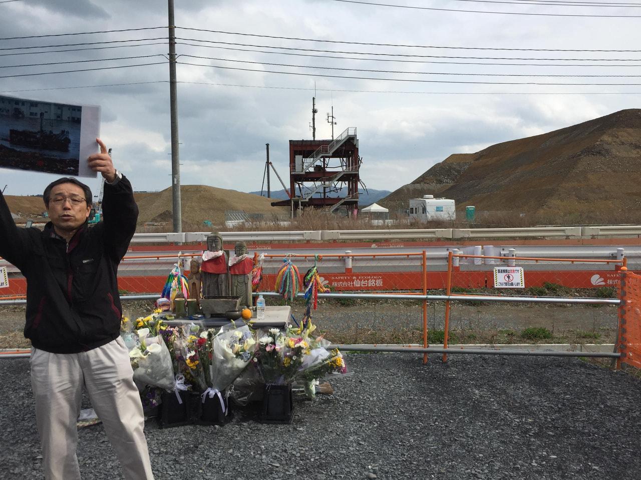 防災センターの前で震災当時の写真を見せながら説明してくださっている佐藤さん